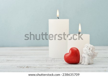 Statuette of small  angel with stone heart and candles over light background - stock photo