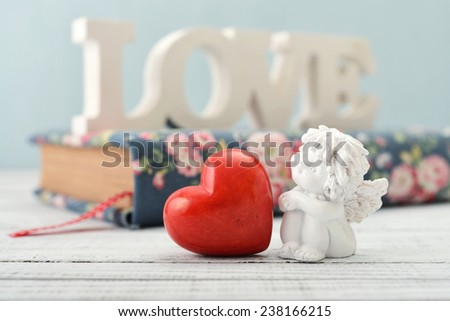 Statuettes of small  angels with stone heart and diary over light background - stock photo