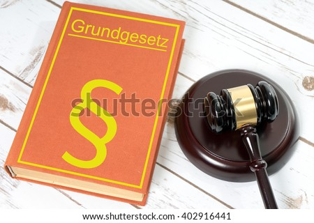 Statute book with the German words fundamental law and Judges gavel / Statute book - stock photo