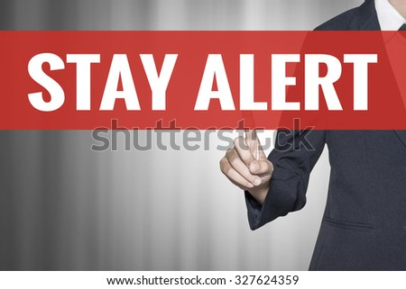 Stay Alert word on virtual screen push by business woman red tab - stock photo