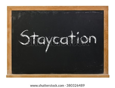 Staycation written in white chalk on a black chalkboard isolated on white