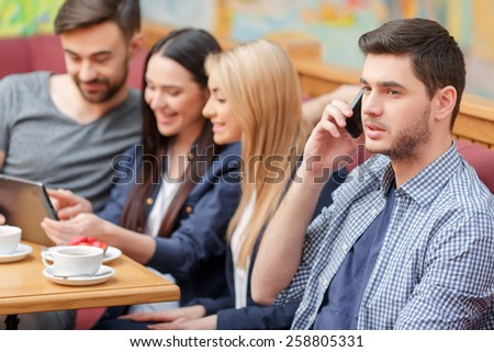 Staying always connected. Handsome young man in casual clothing talking on his mobile phone while witting in the cafe with his friends on the background surfing in the web with digital tablet - stock photo