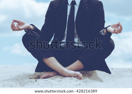 Staying calm. Close-up of businessman meditating while sitting in lotus position on sand and against blue sky - stock photo