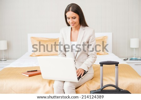 Staying connected anytime. Beautiful young businesswoman in suit working on laptop and smiling while sitting on the bed in hotel room  - stock photo