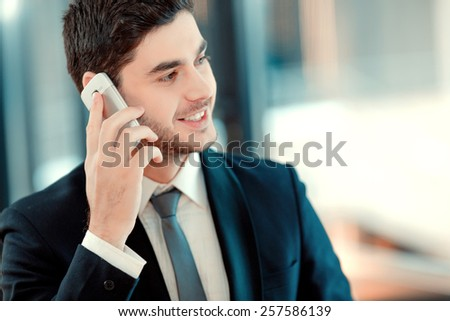 Staying connected. Confident handsome man in formalwear drinking coffee and talking on mobile phone while sitting in restaurant