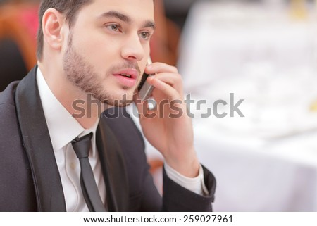 Staying connected. Handsome young businessman in suit talking over his mobile phone while sitting in the luxury restaurant