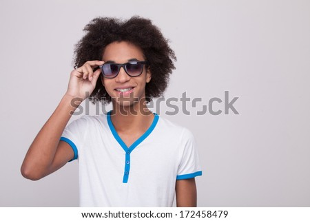 Staying cool! Cheerful teenage African boy adjusting his sunglasses and smiling while standing isolated on grey background - stock photo