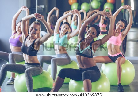 Staying fit. Young beautiful women in sportswear with perfect bodies doing stretching and looking at camera with smile while sitting on fitness balls at gym - stock photo
