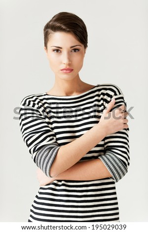 Staying hip. Fashionable young short hair woman in striped clothing keeping arms crossed and looking at camera - stock photo