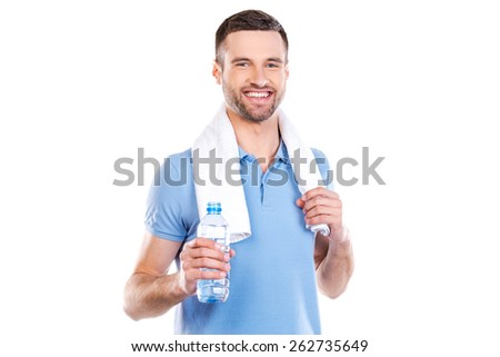 Staying hydrated. Confident young man with towel on shoulders holding bottle with water and smiling while standing against white background  - stock photo