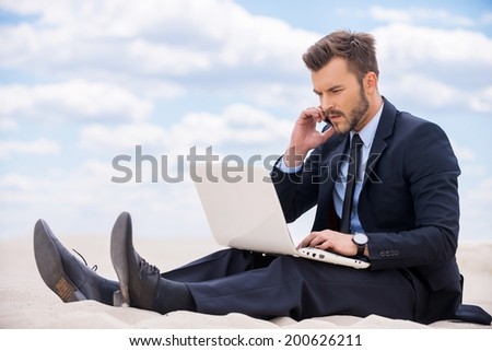 Staying in touch anytime and everywhere. Confident young man in formalwear working on laptop and talking on mobile phone while sitting on sand in desert - stock photo
