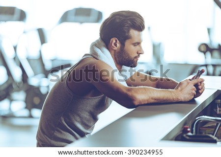 Staying in touch at gym. Side view of handsome young men in sportswear wearing towel on his shoulders and using his smart phone while sitting at bar counter at gym - stock photo