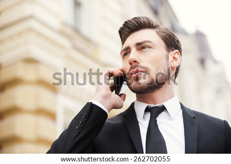 Staying in touch. Low angle view of confident young man in formalwear holding mobile phone and looking away while standing outdoors  - stock photo