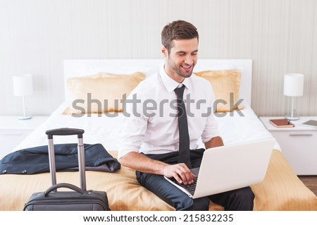 Staying in touch with office. Handsome young man in shirt and tie working on laptop and smiling while sitting on the bed in hotel room  - stock photo