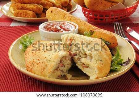 Steak and cheese calzone with bread and mozzarella cheese sticks - stock photo