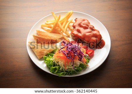 Steak and Spicy sauce on white dish and wooden background