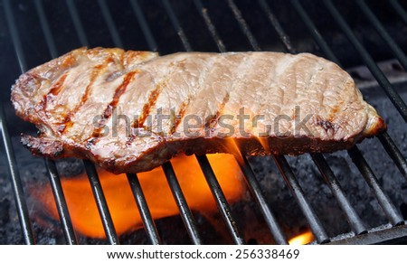 Steak Cooking Over Flames on The Grill