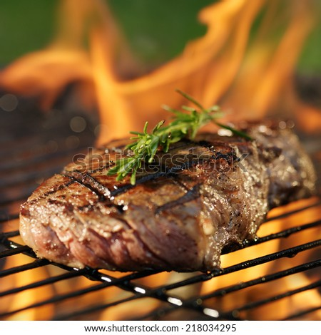 steak cooking over flaming grill - stock photo