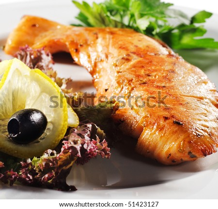 Steak from Filleted Fish (Salmon) with Lemon Slice Olive and Salad on a Plate. Isolated on White Background