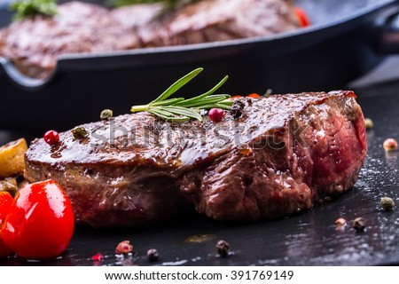 Steak. Grill beef steak. Portions thick beef juicy sirloin steaks on grill teflon pan or old wooden board. - stock photo