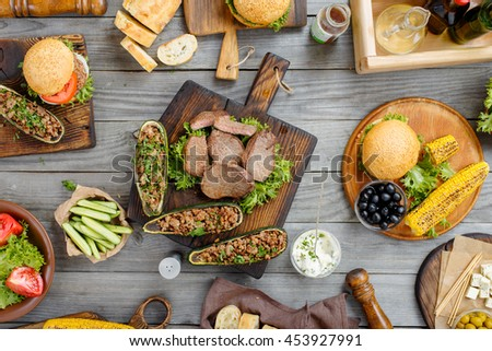 Steak grilled with different food, burgers, stuffed zucchini, vegetables, snacks and sauce on a wooden table, top view. Outdoors Food Concept. Food background - stock photo