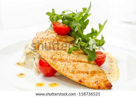 steak is the fried hen with a tomato on a white dish - stock photo