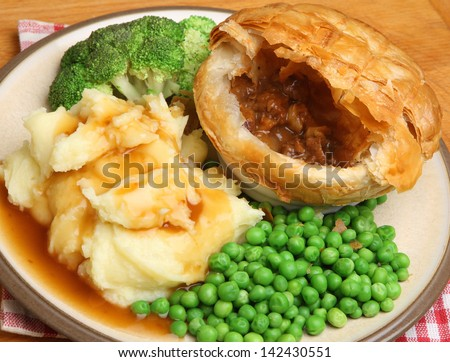 Steak & kidney pie with mashed potato, vegetables and gravy. - stock photo