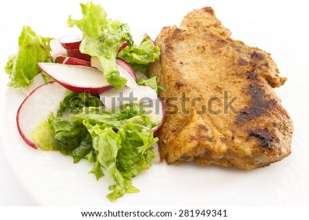 Steak meat grilled with salad made with radish, fresh lettuce and olive oil, in a white plate. Selective focus. - stock photo