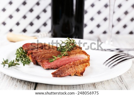 Steak on plate with bottle of wine on wooden background - stock photo