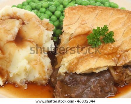 Steak pie with mashed potato, peas and gravy. - stock photo