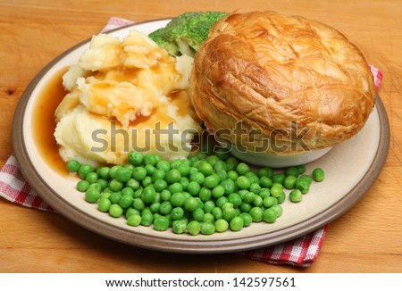 Steak pie with mashed potato, vegetables and gravy. - stock photo