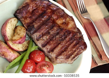 Steak, Potatoes, Beans and Tomatoes with Fork and Napkin - stock photo