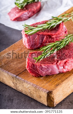 Steak. Raw beef steak. Fresh raw Sirloin beef steak sliced or whole ready for BBQ or grill. Herb - Rosemary decoration. See the full set of 100 amazing photos - stock photo