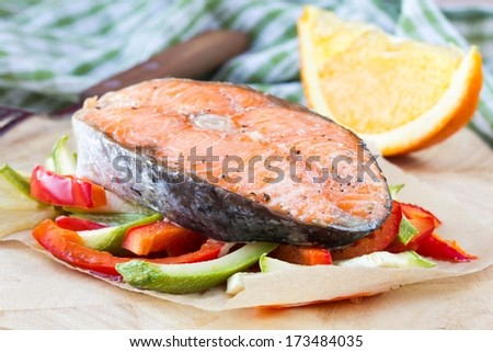 Steak red fish salmon on vegetables, zucchini, sweet pepper, orange, delicious homemade dish - stock photo