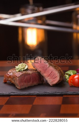 Steak rib-eye garnished with grilled vegetables on stone plate  - stock photo