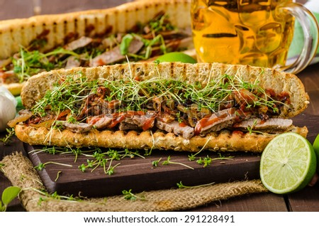 Steak sandwich with herbs, lime and microgreens with little bit kick of hot sriracha souce - stock photo