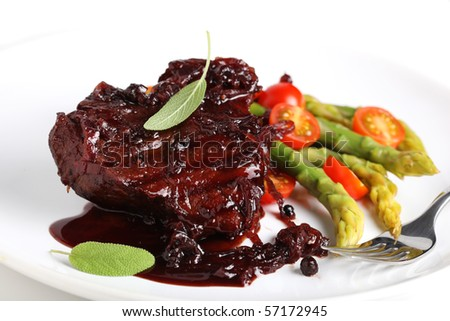 Steak sauce with wine and onions, served with asparagus on a white plate - stock photo