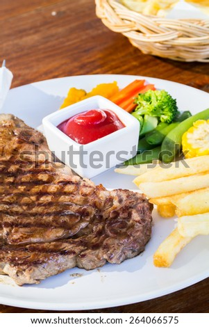 Steak served with french fries and vegetables. - stock photo