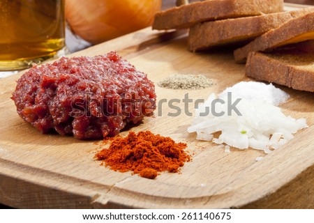 Steak tartar with the fried bread on the wooden trencher - stock photo