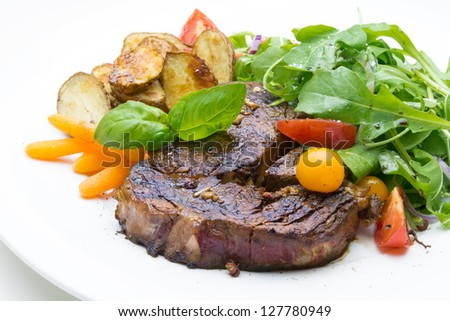 Steak with arugula, tomato, potato and carrot - stock photo