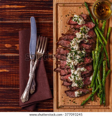 Steak with blue cheese sauce served with asparagus on dark background. - stock photo