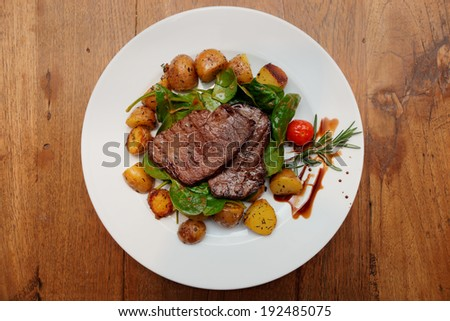 Steak with fried potatoes and spinach on wooden table  - stock photo