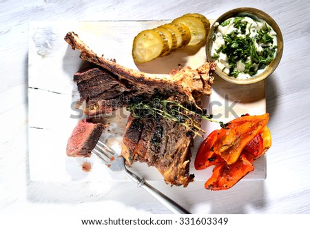 steak with grilled vegetables and sauce on a white background
