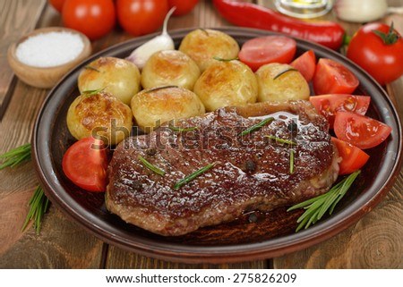 Steak with potatoes on a brown background - stock photo