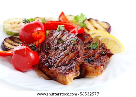 Steak with vegetables on white plate - stock photo