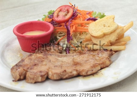 steaks and vegetable salad with french fries.