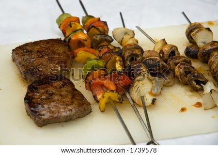 Steaks and vegetables grilled on BBQ and ready to eat - stock photo