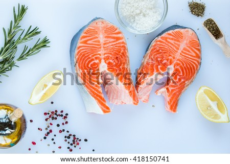 steaks of salmon with a sprigs of rosemary, lemon, pepper,  sea salt,  on a white cutting board, top view. - stock photo