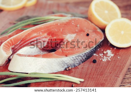 Steaks raw red fish with lemon and spices - stock photo