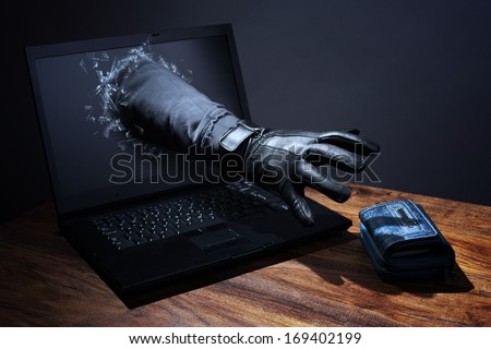 Stealing a purse through a laptop concept for computer hacker, network security and electronic banking security - stock photo